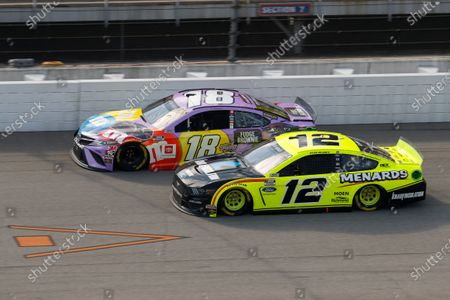 Kyle Busch (18) and Ryan Blaney (12) race during a NASCAR Cup Series auto race at Michigan International Speedway in Brooklyn, Mich