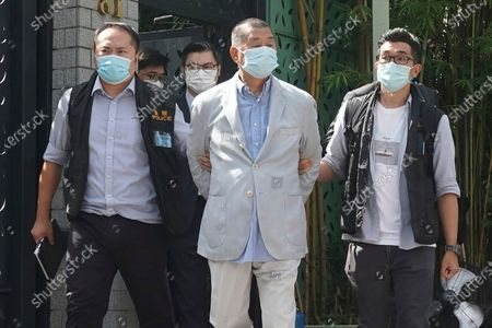 Hong Kong media tycoon Jimmy Lai, center, who founded local newspaper Apple Daily, is arrested by police officers at his home in Hong Kong, . Hong Kong police arrested Lai and raided the publisher's headquarters Monday in the highest-profile use yet of the new national security law Beijing imposed on the city after protests last year