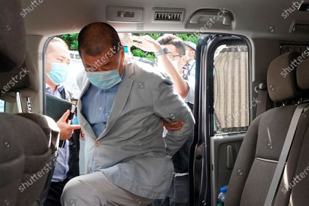 Hong Kong media tycoon Jimmy Lai, who founded local newspaper Apple Daily, gets into a car after being arrested by police officers at his home in Hong Kong, . Hong Kong police arrested Lai and raided the publisher's headquarters Monday in the highest-profile use yet of the new national security law Beijing imposed on the city after protests last year