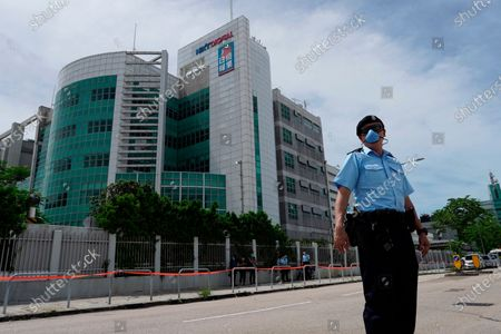 Police officers stand guard outside Apple Daily headquarters as Hong Kong media tycoon Jimmy Lai, who founded local newspaper Apple Daily, is arrested by police officers at his home in Hong Kong, . Hong Kong police arrested Lai and raided the publisher's headquarters Monday in the highest-profile use yet of the new national security law Beijing imposed on the city after protests last year