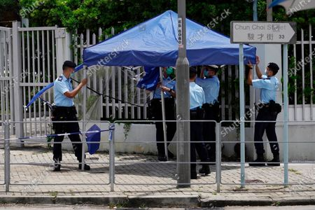 Stock Image of Police officers set up tents outside the Apple Daily headquarters as Hong Kong media tycoon Jimmy Lai, who founded the local newspaper, was arrested by police officers at his home in Hong Kong, . Hong Kong police arrested Lai and raided the publisher's headquarters Monday in the highest-profile use yet of the new national security law Beijing imposed on the city after protests last year