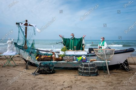 Stock Picture of Every year, the parish of Saint-Vincent de Paul, in Lingreville (50) relocates to the town's beach for an open-air mass, dedicated to workers of the sea and the land and to the dead at sea and named mass of golden shells in reference to the shell, present in Cotentin. This year, the mask was compulsory and the ceremony was almost banned. Despite the restrictions, hundreds of worshipers attended the event.