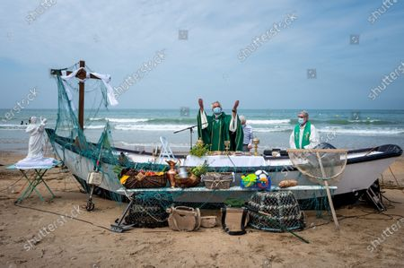 Stock Photo of Every year, the parish of Saint-Vincent de Paul, in Lingreville (50) relocates to the town's beach for an open-air mass, dedicated to workers of the sea and the land and to the dead at sea and named mass of golden shells in reference to the shell, present in Cotentin. This year, the mask was compulsory and the ceremony was almost banned. Despite the restrictions, hundreds of worshipers attended the event.