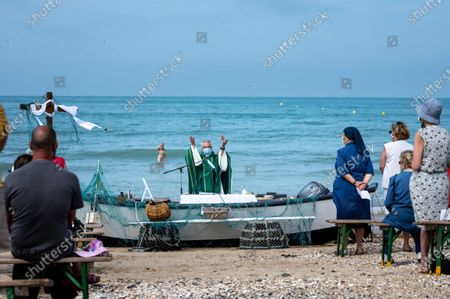 Stock Image of Every year, the parish of Saint-Vincent de Paul, in Lingreville (50) relocates to the town's beach for an open-air mass, dedicated to workers of the sea and the land and to the dead at sea and named mass of golden shells in reference to the shell, present in Cotentin. This year, the mask was compulsory and the ceremony was almost banned. Despite the restrictions, hundreds of worshipers attended the event.