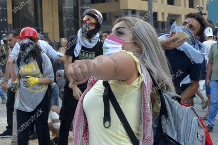 Lebanese anti-government protesters throw stones at security forces at one of the roads leading to the parliament in Beirut, Lebanon, 10 August 2020. Lebanese government resigned amid continuing protests over the Beirut port explosion. Beirut governor said at least 200 people were killed in the explosion on 04 August and dozens are still missing.