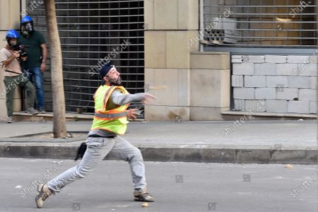 An anti-government protester throws stones at security forces at one of the roads leading to the parliament in Beirut, Lebanon, 10 August 2020. Lebanese government resigned amid continuing protests over the Beirut port explosion. Beirut governor said at least 200 people were killed in the explosion on 04 August and dozens are still missing.