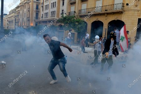 A Lebanese anti-government protester throws back a tear gas bomb fired by security forces during clashes in the area close to the parliament in Beirut, Lebanon, 10 August 2020. Lebanese government resigned amid continuing protests over the Beirut port explosion. Beirut governor said at least 200 people were killed in the explosion on 04 August and dozens are still missing.