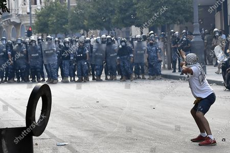 An anti-government protester uses a slingshot to throw stones against Lebanese riot police during a protest at one of the roads leading to the parliament in Beirut, Lebanon, 10 August 2020. Lebanese government resigned amid continuing protests over the Beirut port explosion. Beirut governor said at least 200 people were killed in the explosion on 04 August and dozens are still missing.