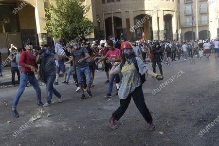 Lebanese anti-government protesters throw stones at security forces at one of the roads leading to the parliament in Beirut, Lebanon, 10 August 2020. According to reports, anti-government protests continued in Lebanon despite the resignation of three ministers and several members of the parliament, as protesters are demand the resignation of the government and all those responsible for the port explosion be held accountable. Beirut governor said at least 200 people were killed in the explosion on 04 August and dozens are still missing.