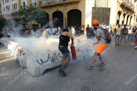 A protester attempt to throw back a tear gas canister during clashes with security forces near the parliament in Beirut, Lebanon, 10 August 2020. According to reports, anti-government protests continued in Lebanon despite the resignation of three ministers and several members of the parliament, as protesters are demanding the resignation of the government and all those responsible for the port explosion be held accountable. Beirut governor said at least 200 people were killed in the explosion on 04 August and dozens are still missing.