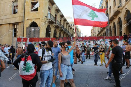 Protesters wave a Lebanese flag during protests near the parliament in Beirut, Lebanon, 10 August 2020. According to reports, anti-government protests continued in Lebanon despite the resignation of three ministers and several members of the parliament, as protesters are demanding the resignation of the government and all those responsible for the port explosion be held accountable. Beirut governor said at least 200 people were killed in the explosion on 04 August and dozens are still missing.