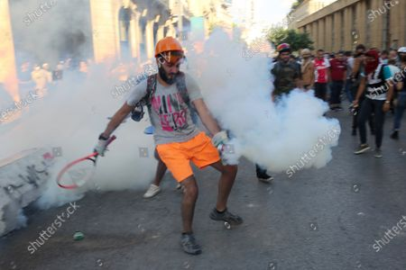 A protester attempts to throw back a tear gas canister during clashes with security forces near the parliament in Beirut, Lebanon, 10 August 2020. According to reports, anti-government protests continued in Lebanon despite the resignation of three ministers and several members of the parliament, as protesters are demanding the resignation of the government and all those responsible for the port explosion be held accountable. Beirut governor said at least 200 people were killed in the explosion on 04 August and dozens are still missing.