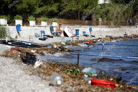 A man rests on a bench by the beach in the Markopoulos area, near Oropos, which is covered by debris washed ashore, from the floods on the island of Euboea
