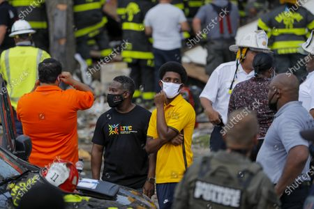Baltimore city council member Brandon Scott, center, looks on in the aftermath of an explosion in Baltimore on . Baltimore firefighters say an explosion has leveled several homes in the city