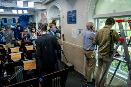Members of the media look outside from the James Brady Press Briefing Room at the White House, in Washington, as a news conference by President Donald Trump was paused by a security incident outside the fence of the White House