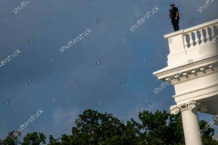 Secret Service police officer stands on the roof of the the White House, in Washington, as a news conference by President Donald Trump was paused