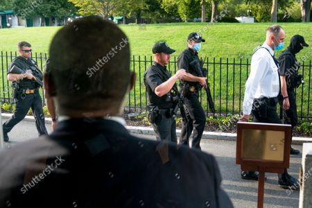 Members of the Secret Service stand guard outside the James Brady Press Briefing Room as President Donald Trump holds a news conference at the White House, in Washington. Trump briefly left because of a security incident outside the fence of the White House