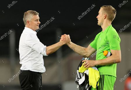 Manchester United's manager Ole Gunnar Solskjaer, left, greets with Copenhagen's goalkeeper Karl-Johan Johnsson, right, after the UEFA Europa League quarterfinal soccer match between Manchester United and FC Copenhagen in Cologne, Germany