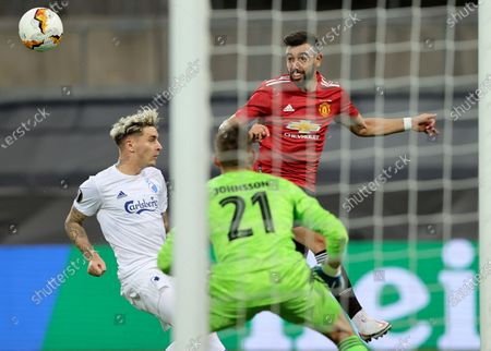 Manchester United's Bruno Fernandes, right, tries to head the ball past Copenhagen's Guillermo Varela, left, and Copenhagen's goalkeeper Karl-Johan Johnsson during the UEFA Europa League quarterfinal soccer match between Manchester United and FC Copenhagen in Cologne, Germany