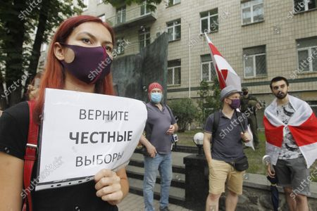 """A woman wearing a mask holds a placard reading """"Bring back fair elections"""", during a rally. Belarusian citizens living in Ukraine held a rally of solidarity with Belarus opposition outside the Embassy of Belarus, protesting vote rigging in the presidential election held in Belarus on the 9th Aug 2020, demanding the presidential election results not to be recognized."""
