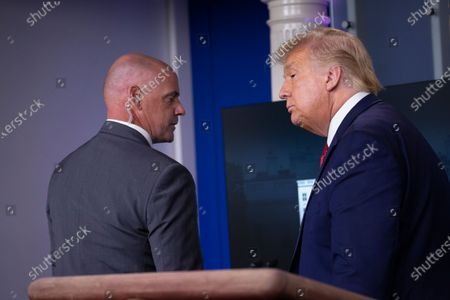 Stock Image of United States President Donald J. Trump is removed from the White House Briefing Room by a US Secret Service agent during a press conference in Washington, DC.