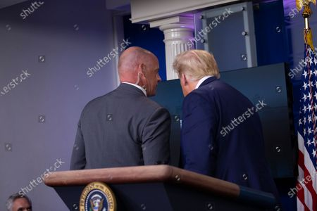 Stock Photo of United States President Donald J. Trump is removed from the White House Briefing Room by a US Secret Service agent during a press conference in Washington, DC.