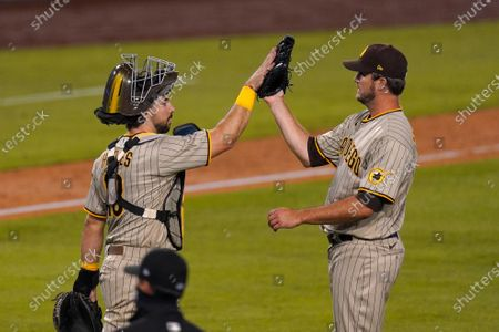 San Diego Padres catcher Austin Hedges, left, and relief pitcher Drew Pomeranz congratulate each other after the Padres defeated the Los Angeles Dodgers 2-1 in a baseball game, in Los Angeles