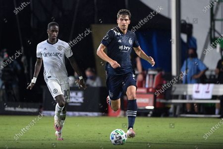 Philadelphia Union midfielder Jamiro Monteiro (10) and Sporting Kansas City midfielder Graham Smith, right, chase after a ball during the second half of an MLS soccer match, in Kissimmee, Fla