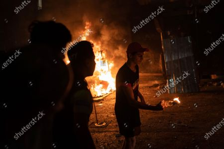 An anti-government protester prepares to throw a molotov cocktail at the riot police, at the end of a demonstration following last week's massive explosion which devastated Beirut, Lebanon