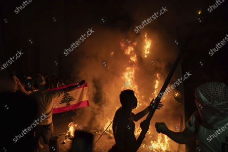 Anti-government protesters burn a barricade next to a wall installed by security forces to block access to the Parliament building, during a demonstration following last week's massive explosion which devastated Beirut, Lebanon