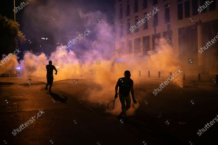 An anti-government protester throws a tear gas canister back to Riot Police using a tennis racket during a demonstration following last week's massive explosion which devastated Beirut, Lebanon