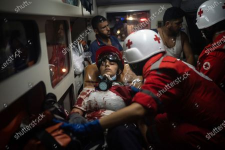 An injured demonstrator is taken by an ambulance after clashes with police during an anti-government protest, following last week's massive explosion which devastated Beirut, Lebanon