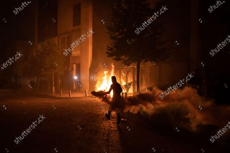 An anti-government protester runs with a tear gas canister to throw back towards Riot Police during a demonstration following last week's massive explosion which devastated Beirut, Lebanon