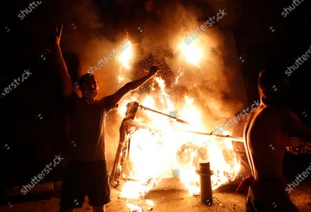 Anti-government protester flashes victory sign, as they burn police metal barrier, during a protest following last week's explosion that killed many and devastated the city, in Beirut, Lebanon