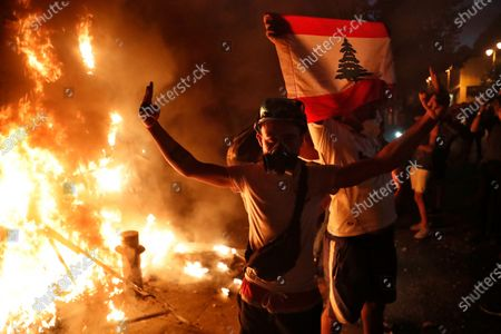 Anti-government protesters hold the Lebanese flag and flash victory sign, as they burn metal police barrier, during a protest following last week's explosion that killed many and devastated the city, in Beirut, Lebanon