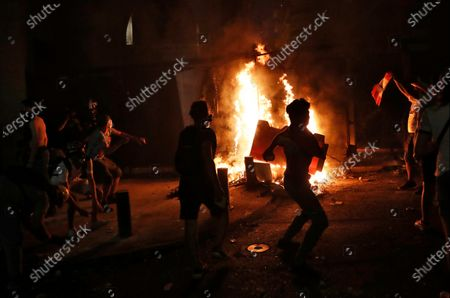 Anti-government protesters throw stones against riot police, during a protest following last week's explosion that killed many and devastated the city, in Beirut, Lebanon