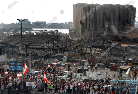 People gather in honor of the victims at the scene of the last week's explosion that killed many and devastated the city, in Beirut, Lebanon