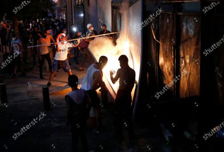Anti-government protesters burn a plastic board as they try to remove metal police barrier, during a protest following last week's explosion that killed many and devastated the city, in Beirut, Lebanon