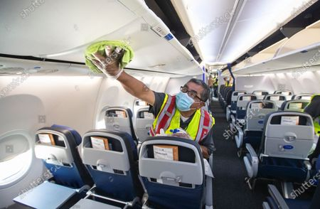 Cleaning supervisor Jose Mendoza disinfects the cabin area of a United Airlines 737 jet before passengers are allowed to board at LAX on Thursday, July 9, 2020 in Los Angeles, CA. (Mel Melcon / Los Angeles Times)