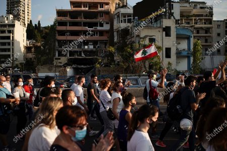People march in honor of the victims of the last week's explosion that killed over 150 people and devastated the city, near the blast site in Beirut, Lebanon