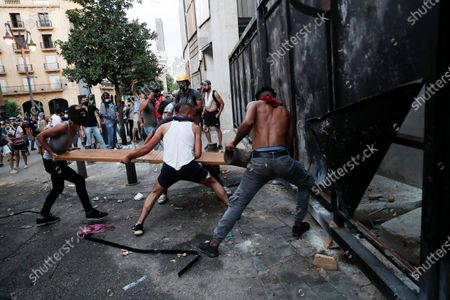 People try to break police barrier during a protest following last week's explosion that killed many and devastated the city, in Beirut, Lebanon, . The massive explosion of nearly 3,000 tons of ammonium nitrate in Beirut's port killed more than 170 people, injured about 6,000 others and caused widespread damage