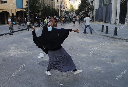 People throw stones during a protest following last week's explosion that killed many and devastated the city, in Beirut, Lebanon, . The massive explosion of nearly 3,000 tons of ammonium nitrate in Beirut's port killed more than 170 people, injured about 6,000 others and caused widespread damage