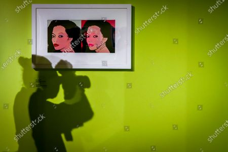 Stock Image of A man takes a photo next to an original cover of Diana Ross during the inauguration of the Andy Warhol Pop Art exhibit at the RCB Galleria in Bangkok, Thailand, 11 August 2020. Running from 12 August to 24 November, the exhibit showcases 128 original artworks and memorabilia from the private collection of Italian art collector Gianfranco Rosini. Andy Warhol Pop Art is divided in four sections showcasing self-portraits and photos, celebrity portraits, magazine and album covers, and silk prints.