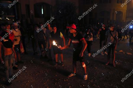 An anti-government protester prepares to throw a molotov cocktail at the riot police, during a protest following last week's explosion that killed many and devastated the city, in Beirut, Lebanon