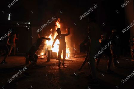 Protesters throw stones and others burn a wall that installed by security forces to prevent protesters from reaching the Parliament building, during a protest following last week's explosion that killed many and devastated the city, in Beirut, Lebanon