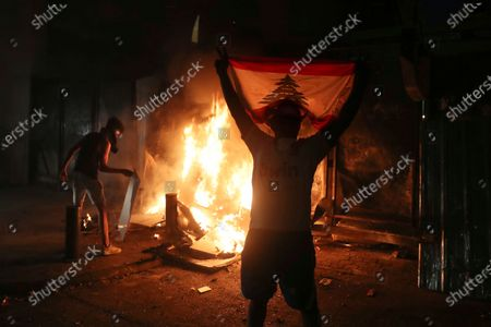 Protester holds up a Lebanese flag as others burn a wall that installed by security forces to prevent protesters from reaching the Parliament building, during a protest following last week's explosion that killed many and devastated the city, in Beirut, Lebanon