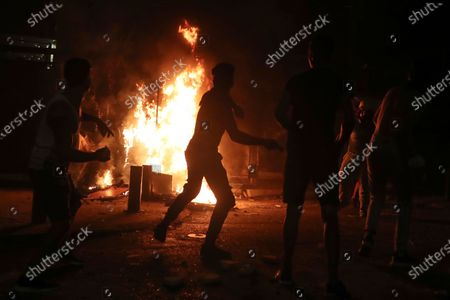 Protesters throw stones as they burn a wall that installed by security forces to prevent protesters from reaching the Parliament building, during a protest following last week's explosion that killed many and devastated the city, in Beirut, Lebanon