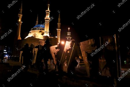 Riot police stand guard in front of the Mohammad al-Amin Mosque, during a protest following last week's explosion that killed many and devastated the city, in Beirut, Lebanon
