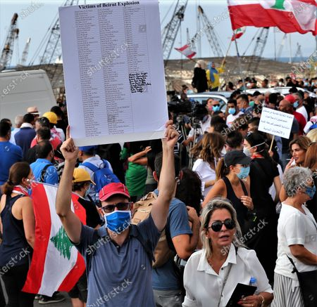An anti-government protestor carries a placard with the names of those killed as they gather near the devastated harbor area to commemorate the victims of the explosion that took place just one week earlier, in Beirut, Lebanon, 11 August 2020. The Lebanese Health Ministry said at least 160 people were killed, and more than 6,000 injured in the Beirut blast that devastated the port area on 04 August and believed to have been caused by an estimated 2,750 tons of ammonium nitrate stored in a warehouse.