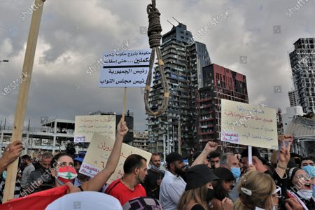 Anti-government protestors carry placards as they gather near the devastated harbor area to commemorate the victims of the explosion that took place just one week earlier, in Beirut, Lebanon, 11 August 2020. The Lebanese Health Ministry said at least 160 people were killed, and more than 6,000 injured in the Beirut blast that devastated the port area on 04 August and believed to have been caused by an estimated 2,750 tons of ammonium nitrate stored in a warehouse